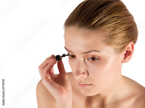 young woman putting make up. Isolated