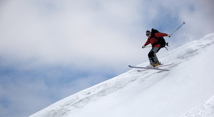 Skier jumping from the edge of snow ridge