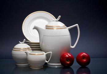 White china tea-set and apples on blue