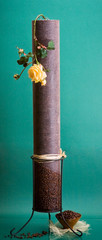 Tall fruit candle with coffee beans and rose on green