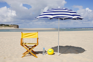 chair, water bottle, ball on the beach