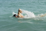 A man swimming front crawl in the sea. poster