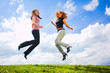 Two jumping girls on blue sky