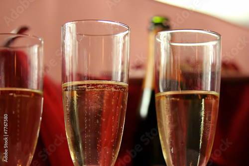 champagne glasses with bottle on background