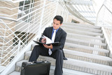 Business Man on Stairs Reviewing Notes poster
