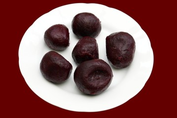 peeled and cooked beetroot on a plate of crockery