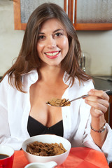 Sexy brunette eating breakfast