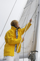 Young man standing on yacht in sea