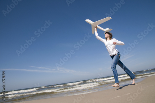Teenager with plane on the beach