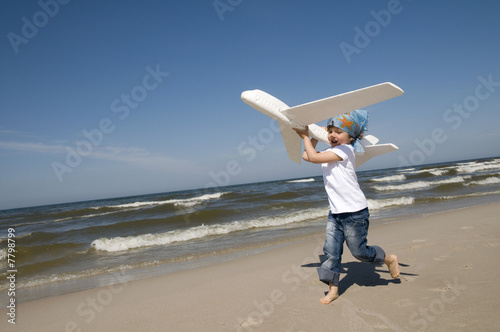 Little girl playing with plane on the beach