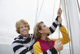 Young couple holding rigging on sailboat, portrait