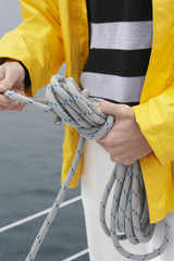 Young man tying rope on yacht, mid section