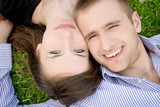 Smiling young couple is cuddle on a green meadow poster