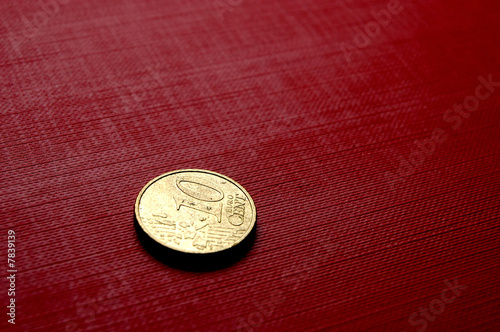 Gold coin on red surface