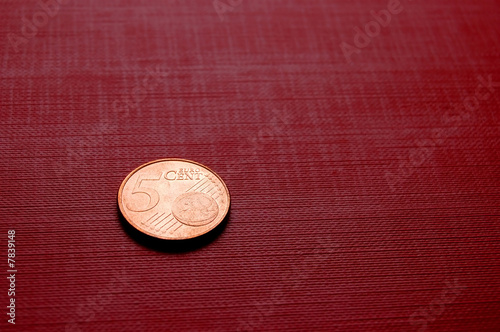 Coin on red surface