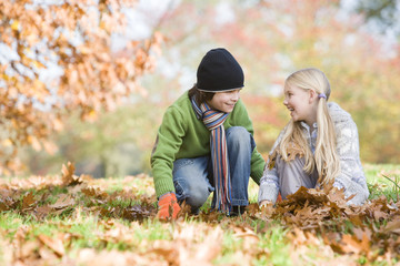 Two children collecting leaves