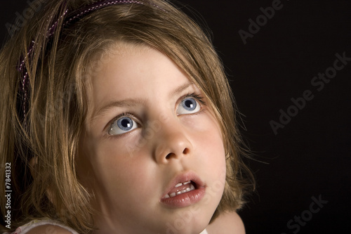 Shot of a young blonde girl with blue blue eyes looking up