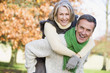 Senior man giving woman piggyback ride - 7841541