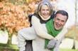Leinwanddruck Bild - Senior man giving woman piggyback ride
