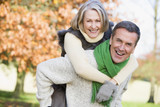 Senior man giving woman piggyback ride - Fine Art prints
