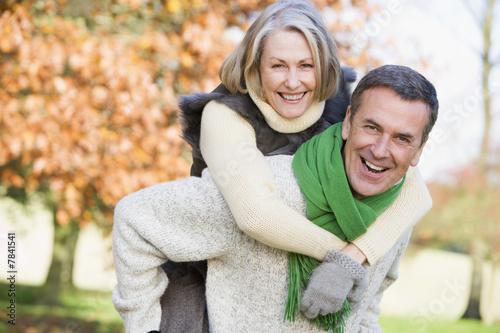 Leinwanddruck Bild Senior man giving woman piggyback ride