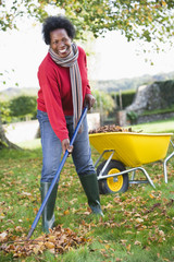 Mature woman collecting leaves in garden