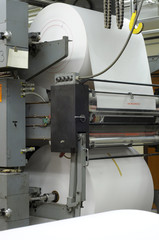 Large rolls of paper on a printing press
