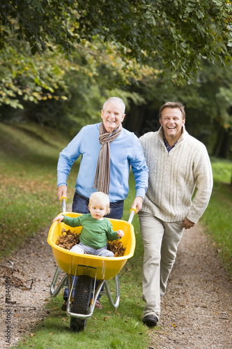 Grandfather with grandson and son pushing wheelbarrow