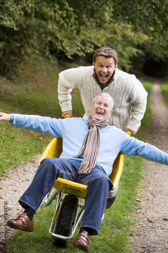 Grown up son pushing father in wheelbarrow