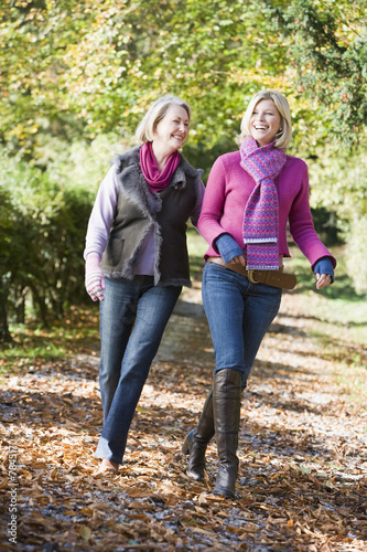 Mother and grown up daughter on walk through woods