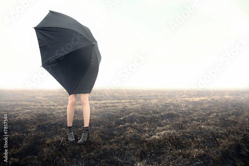 girl with umbrella on black field