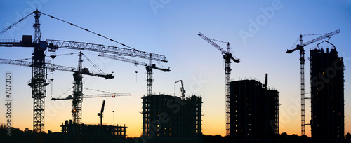 construction cranes silhouette sunset - 7873131