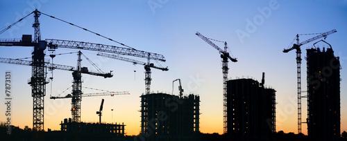 Leinwanddruck Bild construction cranes silhouette sunset