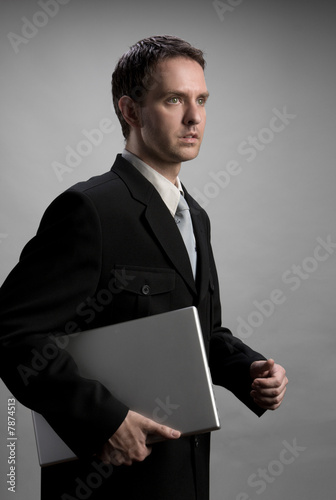Man holding laptop, walking