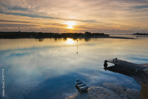 Winter Sunrise over a Glassy River with Boat and Jetty