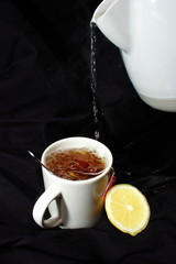 Bubbling Lemon Tea Pour with Black Cloth Background