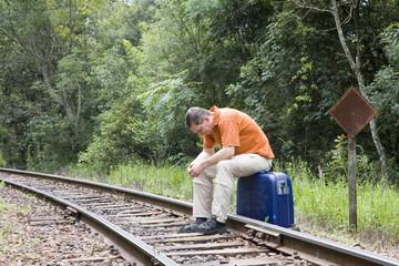 Mann sitzt auf Gleisen