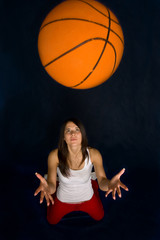 Pretty woman playing basketball against a blue background