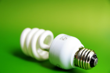 Compact fluorescent light bulb, closeup on green .background