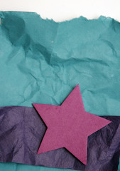 Crumpled green and blue paper and star