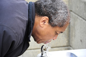 African american man drinking from a water fountain.