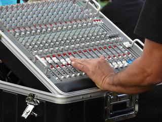 Main de technicien réglant une console.