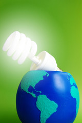 light bulb in an earth globe, on green background