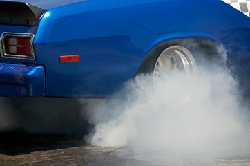 Smoke from the tires of a blue racer 1