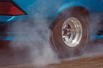 Smoke from the tires of a blue-green racer
