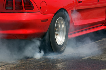 Smoke from the tires of a red racer