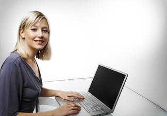 Junge blonde Frau am Computer arbeitend