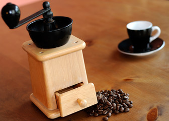 Espresso cup and saucer; grinder and coffee beans