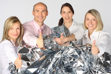 Businessteam with a lot of silver foil showing thumbs