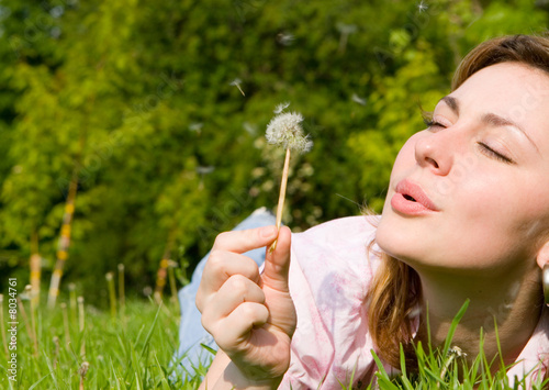 happy girl blowing on the dandelion